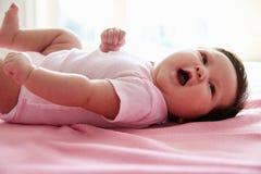 Bébé mignon s'étendant sur la couverture rose image stock