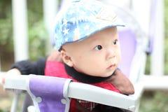 Bébé mignon s'asseyant dans la poussette photo stock