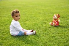 bébé mignon s'asseyant sur l'herbe verte avec son t Photographie stock