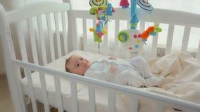 Bébé mignon se situant dans le berceau avec le carrousel de rotation de jouet clips vidéos