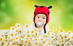 Bébé mignon se situant dans le lit sur la couverture blanche dans le chapeau de coccinelle Photographie stock libre de droits