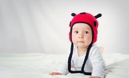 Bébé mignon se situant dans le lit sur la couverture blanche dans le chapeau de coccinelle Images libres de droits