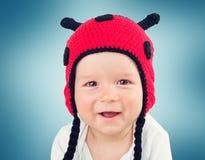 Bébé mignon se situant dans le lit sur la couverture blanche dans le chapeau de coccinelle Image stock