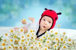 Bébé mignon se situant dans le lit sur la couverture blanche dans le chapeau de coccinelle Photo stock