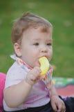 Bébé, moins que jouer an avec la banane de jouet Images stock