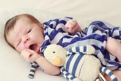 Bébé nouveau-né avec une écharpe et un jouet rayés, fond mou de foyer photo libre de droits