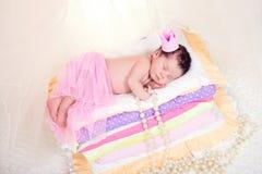 Bébé nouveau-né dans une couronne dormant sur le lit des matelas Princesse féerique et le pois Image stock