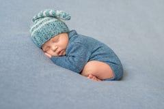 Bébé nouveau-né de sommeil dans la salopette et le chapeau bleus photo stock