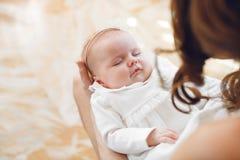 Bébé nouveau-né dormant sur les mains de la mère Image stock