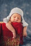 Bébé nouveau-né en bonne santé dans le chapeau drôle dormant dans le panier Image libre de droits