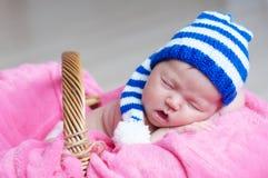 Bébé nouveau-né heureux mignon dans le chapeau tricoté rayé dormant sur la couverture rose Portrait infantile de sommeil Photos stock