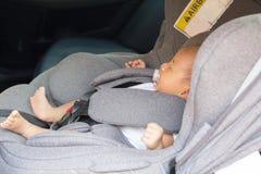 Bébé nouveau-né mignon asiatique dormant dans le siège de voiture moderne Images libres de droits
