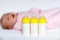 Bébé nouveau-né mignon avec des bouteilles de soins Allaiter au biberon Photos stock