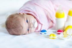 Bébé nouveau-né mignon avec des bouteilles de soins et tétine Photo stock