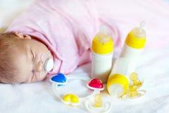 Bébé nouveau-né mignon avec des bouteilles de soins et tétine Image stock