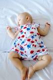 Bébé nouveau-né paisible se trouvant sur un lit photos stock