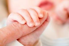 Bébé nouveau-né, plan rapproché des doigts des doigts en main de la mère photographie stock libre de droits