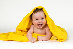 Bébé nouveau-né se couchant et souriant dans une serviette jaune Image stock