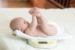 Bébé nouveau-né sur la balance photographie stock