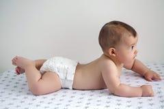 Bébé nu dans des couches-culottes se trouvant sur son ventre photographie stock