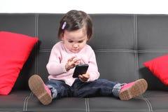 Bébé occasionnel s'asseyant sur un divan touchant un téléphone portable photographie stock libre de droits