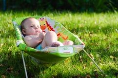 Bébé paisible dans la chaise de basculage sur la nature Images stock