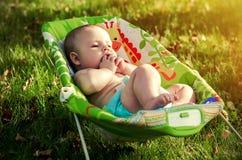 Bébé paisible dans la chaise de basculage sur la nature Photographie stock libre de droits