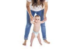 Bébé prenant des premières étapes avec l'aide de mère sur le fond blanc Photographie stock