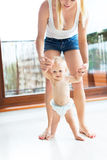 Bébé prenant des premières étapes avec l'aide de mères Photographie stock