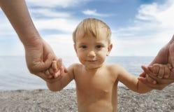 Bébé retenant les mains de son père Images stock