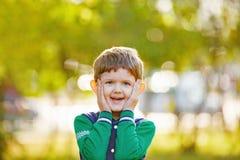 Bébé riant tenant sa tête dans des ses mains avec un lo étonné Image libre de droits