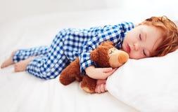 Bébé roux adorable d'enfant en bas âge dans des pyjamas de flanelle dormant avec le jouet de réchauffeur de peluche photos libres de droits
