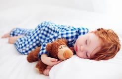 Bébé roux adorable d'enfant en bas âge dormant avec le jouet de peluche dans des pyjamas de flanelle photos stock