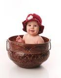 Bébé s'asseyant dans un bac de fleur Images stock