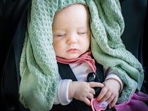 Bébé s'asseyant dans un siège de voiture de bébé dormant après un long tour de voiture Photos stock