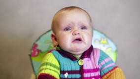 Bébé s'asseyant sur la chaise du ` s d'enfants dans la maison et pleurer clips vidéos