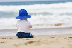 Bébé s'asseyant sur la plage blanc d'isolement de vue arrière Image stock