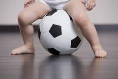 Bébé s'asseyant sur le ballon de football Photos libres de droits