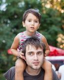Bébé s'asseyant sur le col de son père Image stock