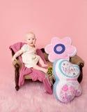 Bébé s'asseyant sur le divan Photo stock