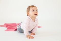 Bébé s'asseyant sur le plancher d'isolement au-dessus du fond blanc Photo libre de droits