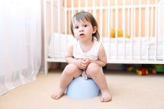 Bébé s'asseyant sur le pot dans la maison Image stock