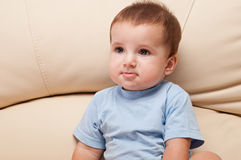 Bébé s'asseyant sur le sofa Image stock