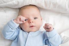 Bébé se couchant sur l'enfant en bas âge arrière et heureux dans la combinaison recherchant Portrait d'un bébé mignon se couchant image stock