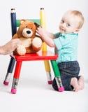 Bébé se mettant à genoux avec Teddy Bear sur la chaise Photo stock