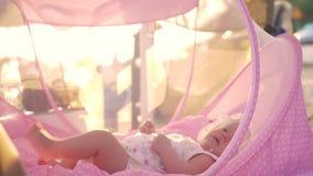 Bébé se situant dans le berceau rose extérieur banque de vidéos
