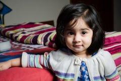 Bébé se tenant avec le lit photo stock