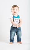 Bébé se tenant tenant des mains semblant étonnées Photographie stock