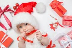 Bébé se trouvant avec des présents dans le chapeau de Santa sur le fond blanc Images stock