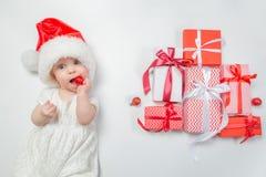 Bébé se trouvant avec des présents dans le chapeau de Santa sur le fond blanc Image stock